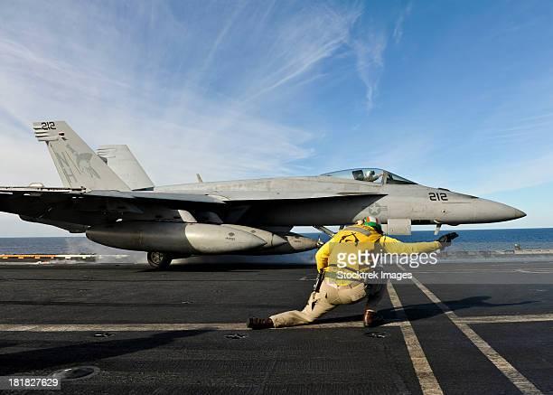 A shooter signals to launch an F/A-18E Super Hornet aboard USS Nimitz.