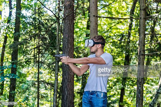 Shooting man in virtual reality headset playing video game
