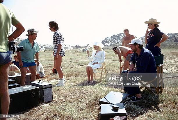 Shooting Of The Film 'Liza' By Marco Ferreri Attitude de Catherine DENEUVE en tailleur blanc et capeline assortie Yves SAINT LAURENT en tongs fumant...
