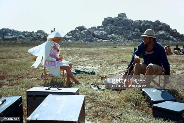 Shooting Of The Film 'Liza' By Marco Ferreri Attitude de Catherine DENEUVE en tailleur blanc et capeline assortie Yves SAINT LAURENT pieds nus assise...
