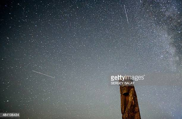 Shooting stars cross the night sky over a wooden idol near the village of Ptich some 25km away from Minsk during the peak of the annual Perseid...