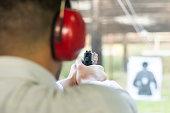 Shooting with Gun at Target in Shooting Range. Man Practicing Fire Pistol Shooting.Shooting with Gun at Target in Shooting Range. Man Practicing Fire Pistol Shooting.
