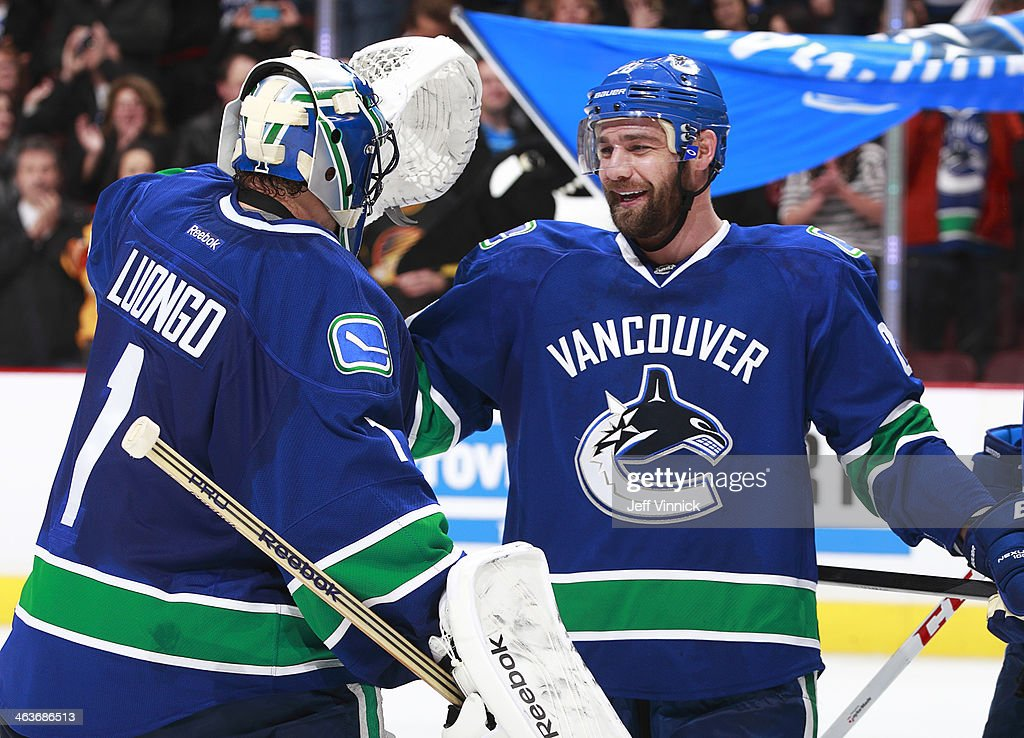 Shootout heroes <a gi-track='captionPersonalityLinkClicked' href=/galleries/search?phrase=Roberto+Luongo&family=editorial&specificpeople=202638 ng-click='$event.stopPropagation()'>Roberto Luongo</a> #1 and Chris Higgins #20 of the Vancouver Canucks celebrate a victory over the Calgary Flames during their NHL game at Rogers Arena January 18, 2014 in Vancouver, British Columbia, Canada. Vancouver won 3-2.