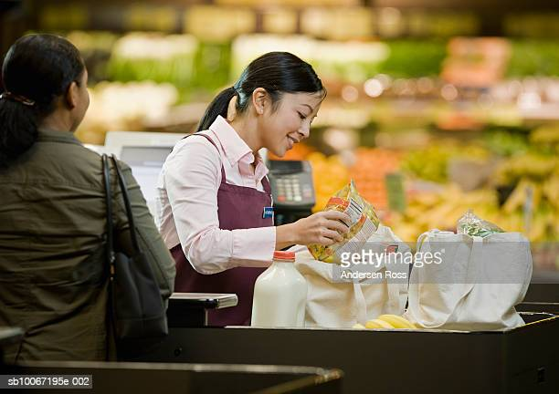 Shop assistance checking groceries at checkout