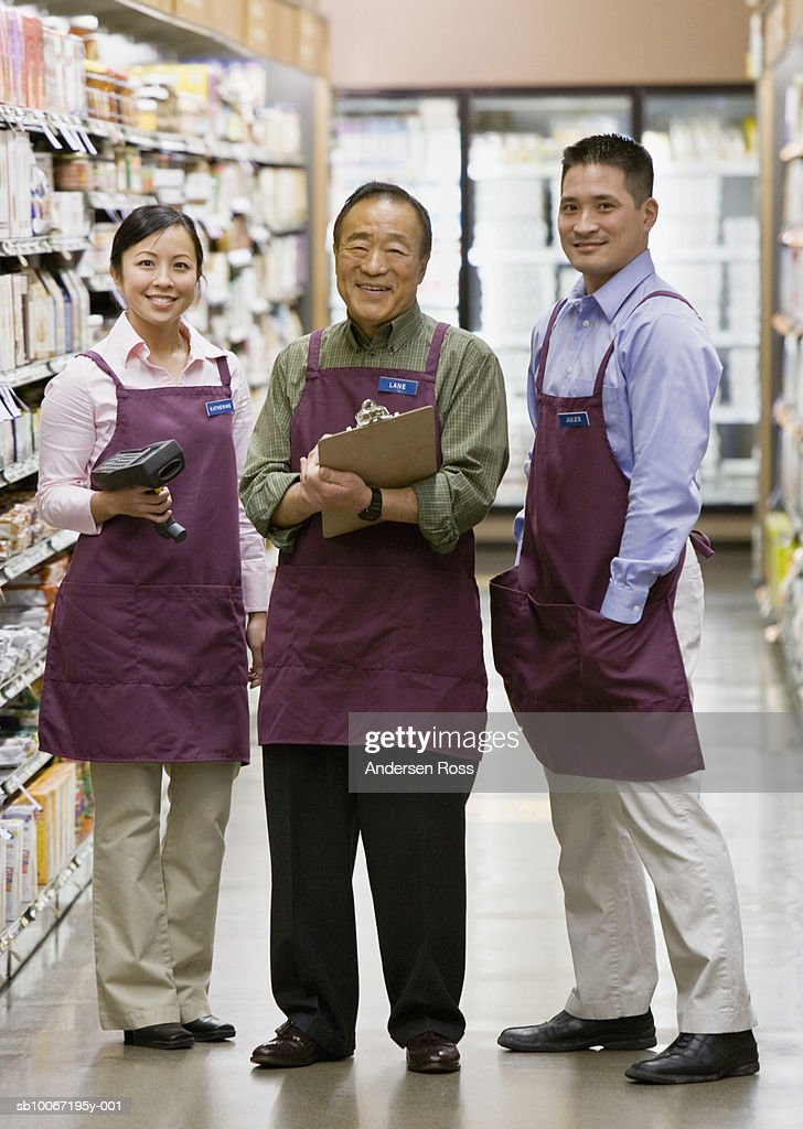 Shop assistance checking groceries at rack, smiling, portrait : Stock Photo