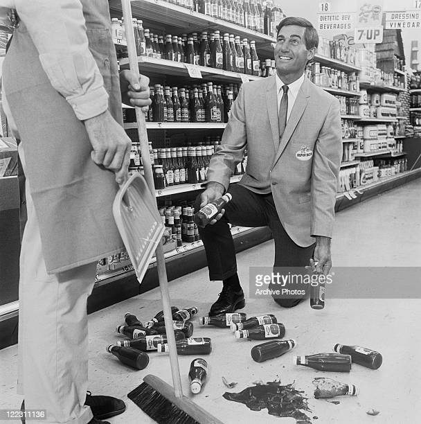 Shop assistance kneeling by fallen bottles, cleaner holding dustpan and broom standing beside