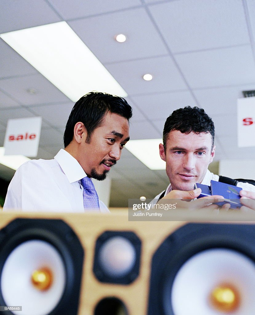 Shop assistant demonstrating personal stereo for customer : Stock Photo