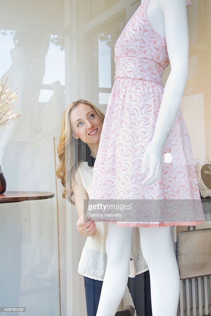 Shop assistant dressing mannequin : Stock Photo