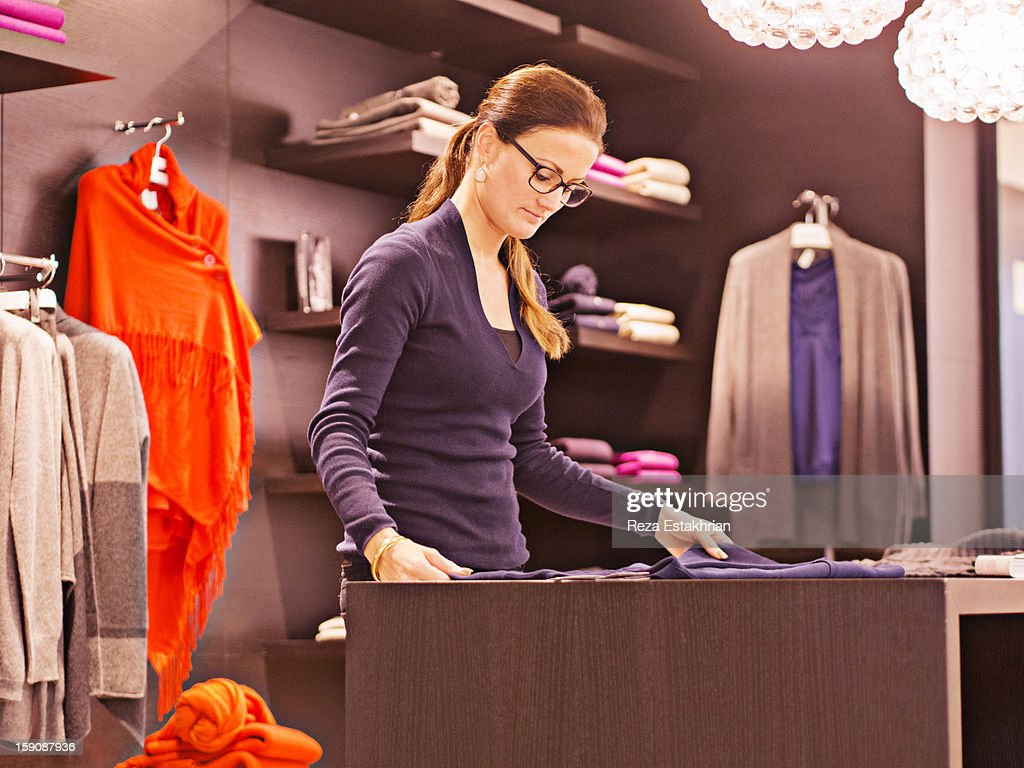 Shop assistant folds sweaters : Stock Photo