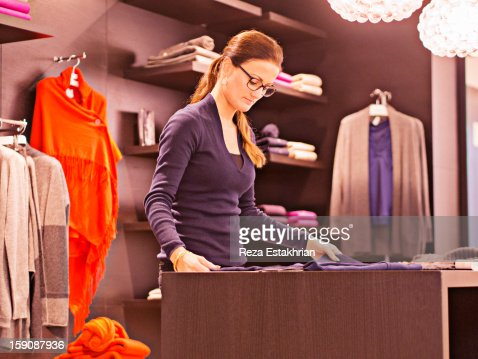 Shop assistant folds sweaters : Bildbanksbilder