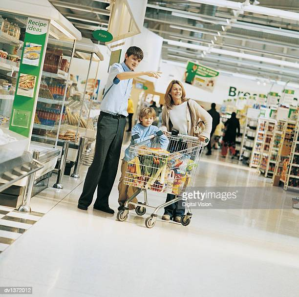 Shop Assistant Giving Advice to a Mother and Son in a Supermarket