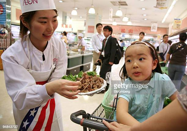 A shop assistant hands out samples of beef imported from the United States at an Aeon Co supermarket in Tokyo Japan on Wednesday April 30 2008 Japan...