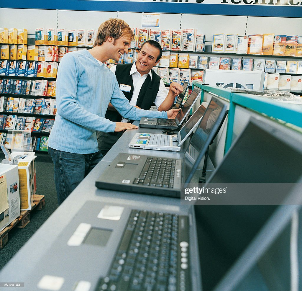 Shop Assistant Helping a Customer With a Laptop in a Computer Shop : Stock Photo