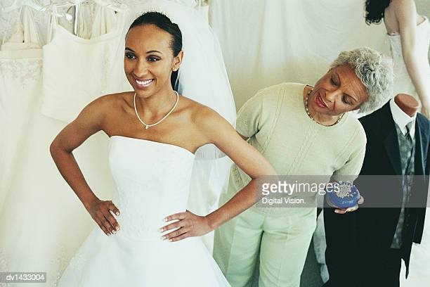Shop Assistant Helping a Woman Try on a Wedding Dress in a Clothes Shop