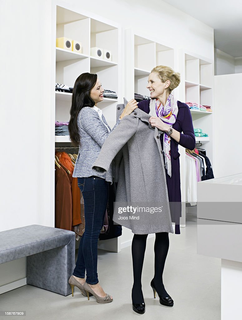 shop assistant helping woman with her coat : Stock Photo