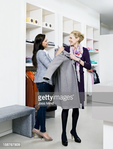shop assistant helping woman with her coat