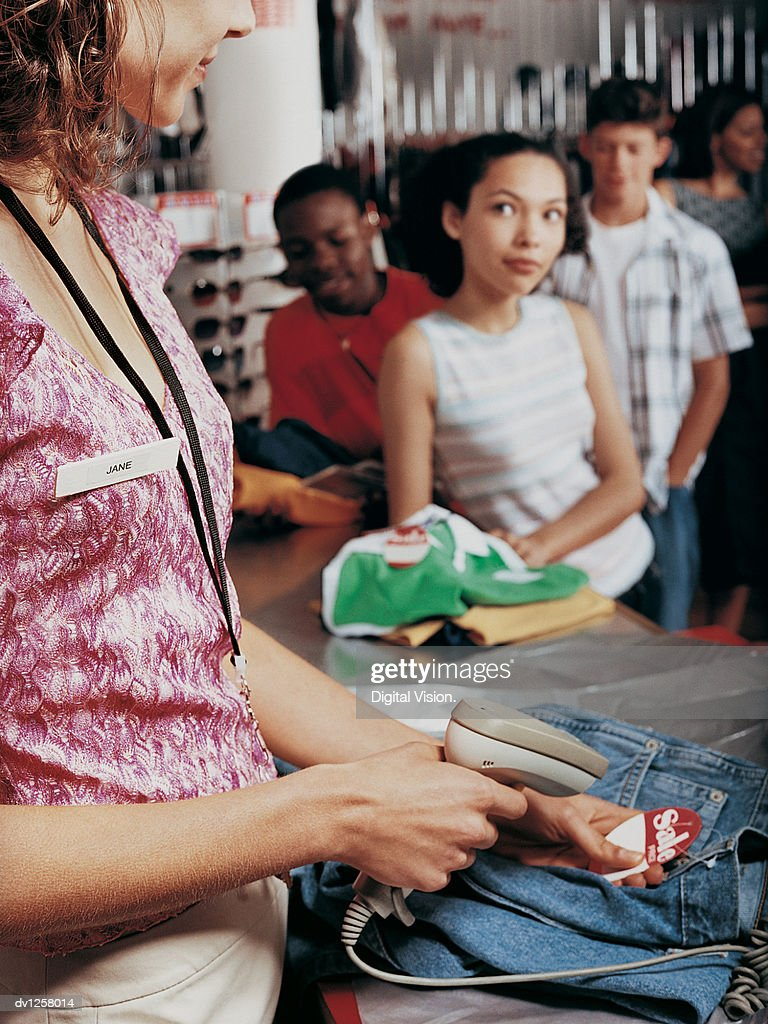 shop assistant holding a barcode reader to a pair of jeans at a shop assistant holding a barcode reader to a pair of jeans at a clothes shop checkout