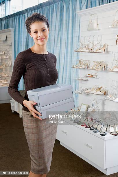 Shop assistant holding shoe boxes in wedding shop, portrait