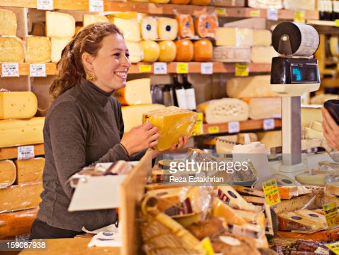 Shop assistant in cheese shop smiles at customer : Foto de stock