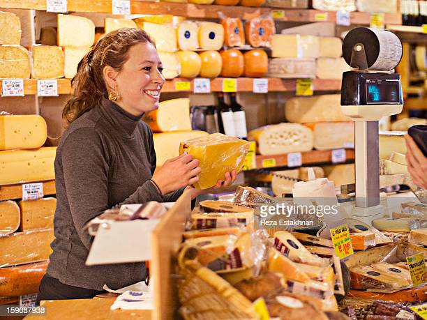 Shop assistant in cheese shop smiles at customer