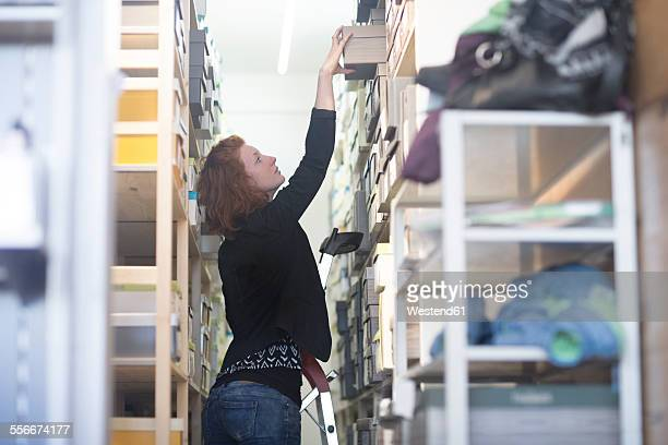 Shop assistant in shoe shop taking box from shelf