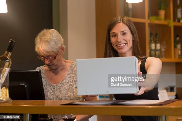 Shop assistant in wine shop holding box looking at camera smiling