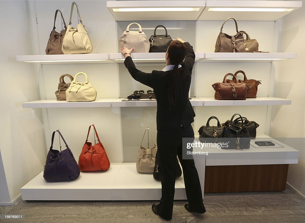 """A shop assistant is seen adjusting a Bally 'Piaff"""" handbag, produced by Bally the Swiss luxury brand, in their store in the town of Davos, Switzerland, on Saturday, Jan. 19, 2013. Next week the business elite gathers in the Swiss Alps for the 43rd annual meeting of the World Economic Forum in Davos, the five day event runs from Jan. 23-27. Photographer: Chris Ratcliffe/Bloomberg via Getty Images"""