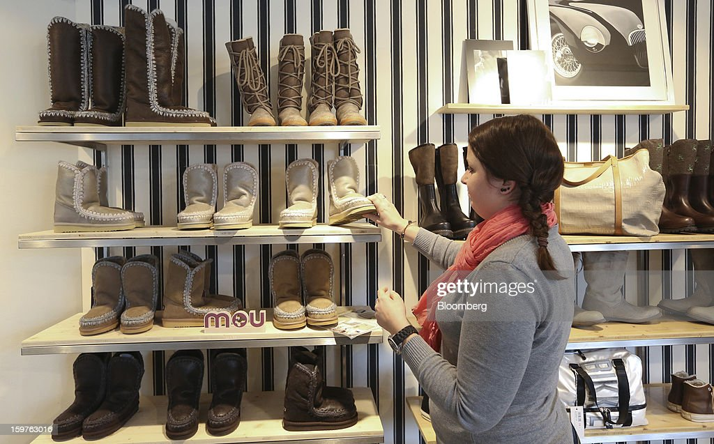 A shop assistant is seen arranging a footwear display in the Allenbach clothes store in this arranged photograph in the town of Davos, Switzerland, on Saturday, Jan. 19, 2013. Next week the business elite gathers in the Swiss Alps for the 43rd annual meeting of the World Economic Forum in Davos, the five day event runs from Jan. 23-27. Photographer: Chris Ratcliffe/Bloomberg via Getty Images