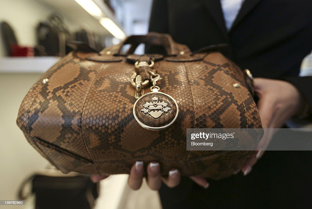 A shop assistant is seen holding a Bally designed handbag finished in Python skin, produced by Bally the Swiss luxury brand, in this arranged photograph at their store in the town of Davos, Switzerland, on Saturday, Jan. 19, 2013. Next week the business elite gathers in the Swiss Alps for the 43rd annual meeting of the World Economic Forum in Davos, the five day event runs from Jan. 23-27. Photographer: Chris Ratcliffe/Bloomberg via Getty Images