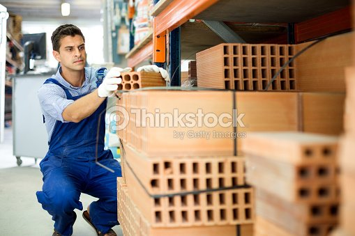 Shop assistant man is checking quality of bricks : Stock Photo