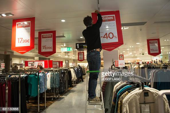 A shop assistant of el corte ingles department store displays signs announcing discounts on the - El corte ingles stores ...