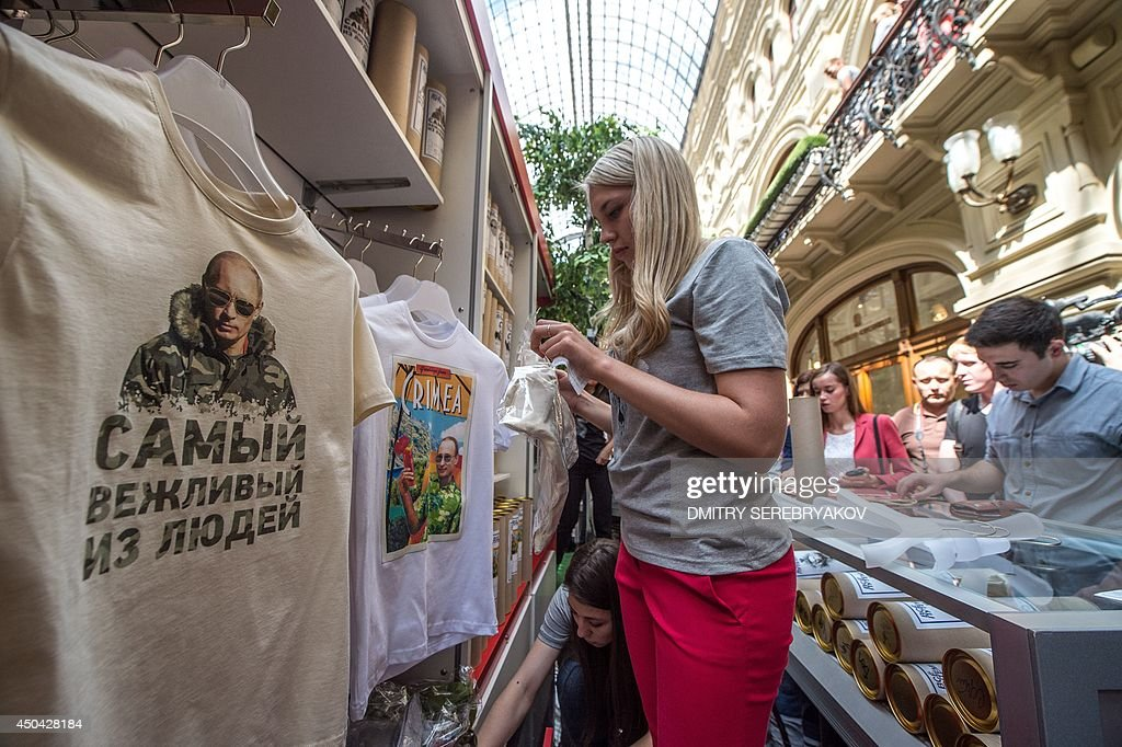 A shop assistant packs one of the T-shirts with images of Russia's President Vladimir Putin being displayed for sale at GUM, one of the oldest department stores in central Moscow, on June 11, 2014.