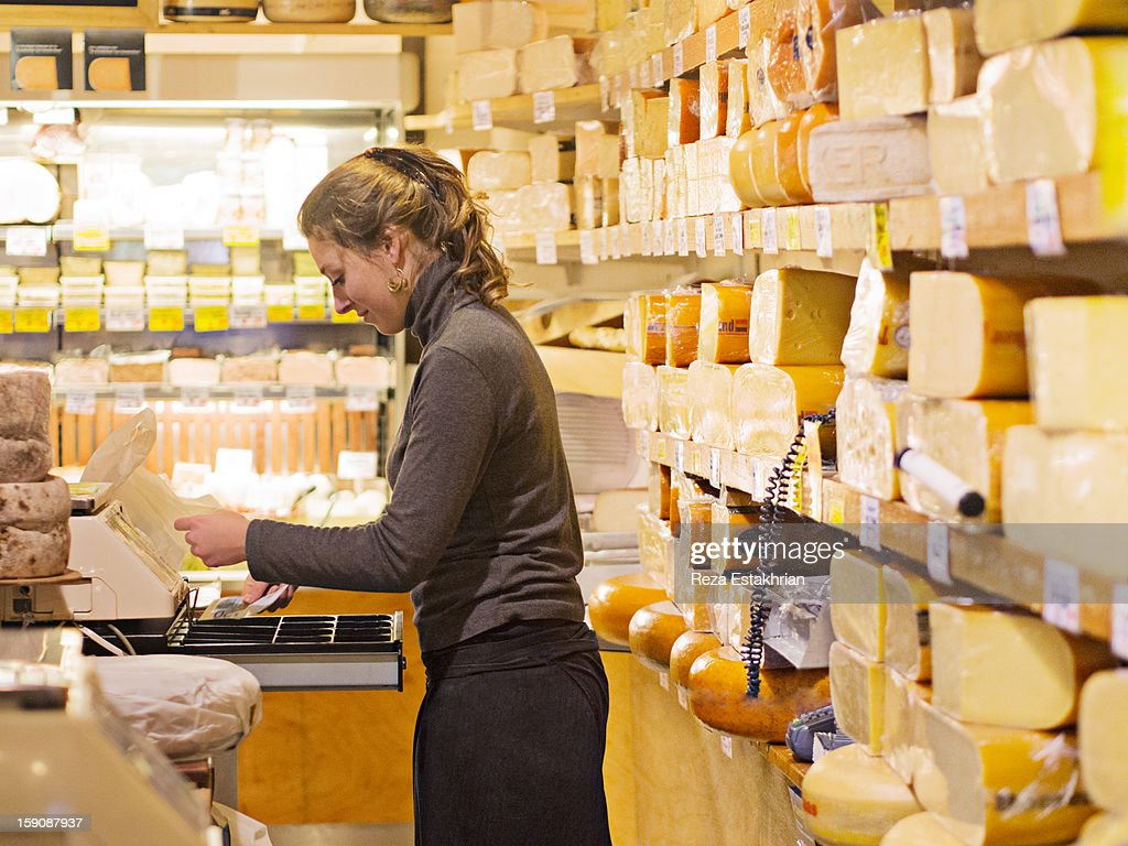 Shop assistant places cash in register : Stock Photo