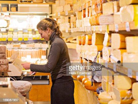 Shop assistant places cash in register : Stock Photo