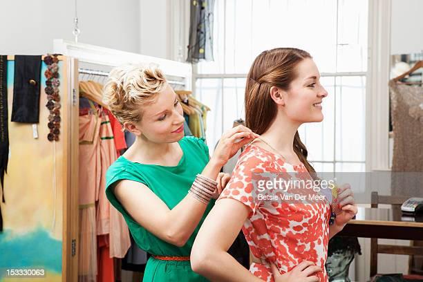 Shop assistant putting necklace on clients neck.
