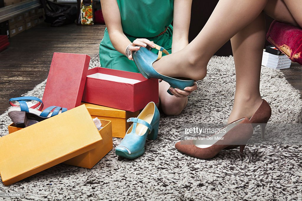 Shop assistant putting shoes on clients foot.