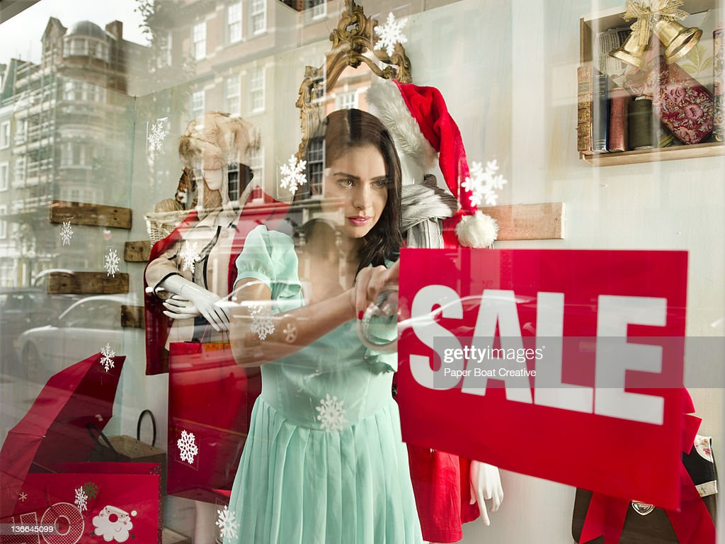shop assistant putting up a sale sign on window