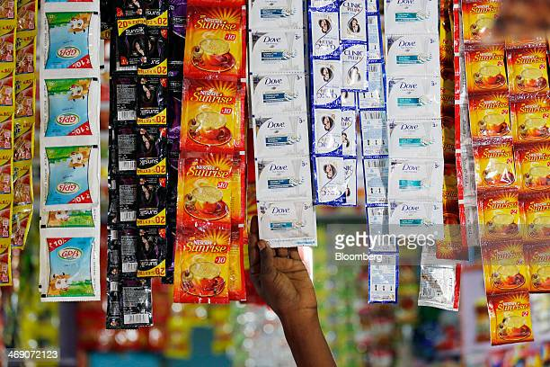 A shop assistant reaches for a sachet of Hindustan Unilever Ltd's Dove Dryness Care Shampoo center displayed next to sachets of Nestle India Ltd's...