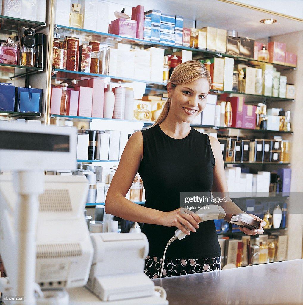 Shop Assistant Scanning Perfume at Cash Register : Photo
