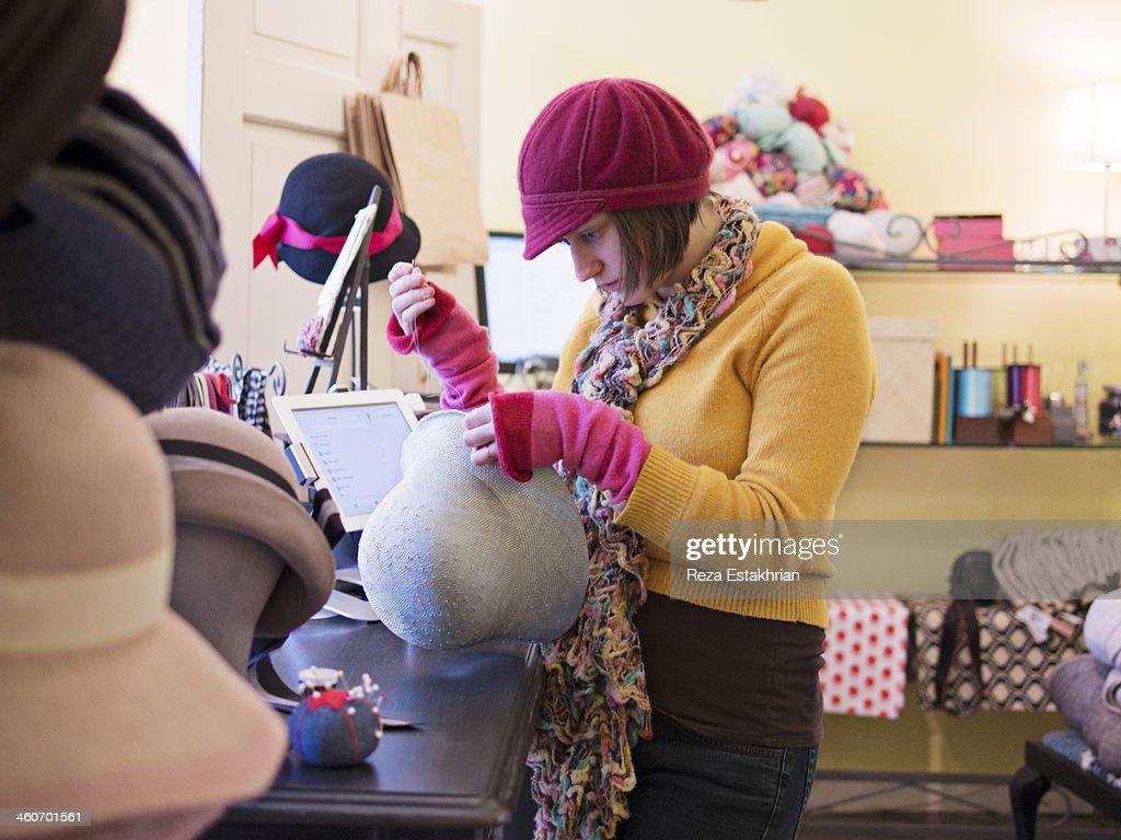 Shop assistant sews trim on hat