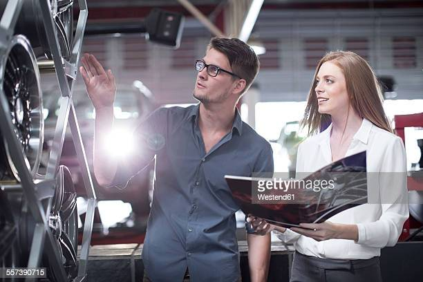Shop assistant showing woman in tyre shop the selection of available tyres