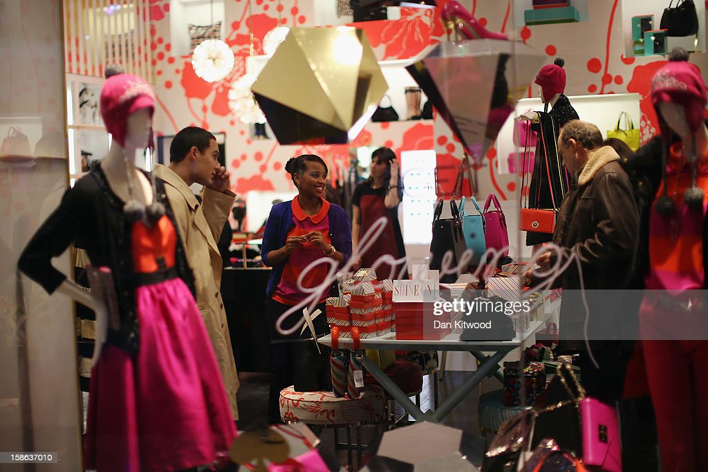 A shop assistant speaks with customers in Westfield Shopping centre in West London on December 22, 2012 in London, England. Today is the final Saturday before Christmas.