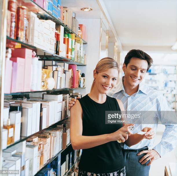 Shop Assistant Sprays Perfume Sample as a Man Stands With his Hand on his Hip and his Arm Around Her