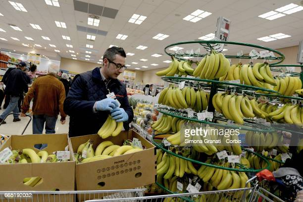 A shop assistant stacks produce in the fruit and vegetable section as Italian supermarket chain Esselunga opens its first store in Rome in Via...