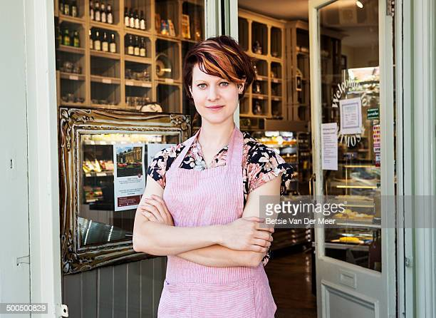 shop assistant standing in front of deli shop.