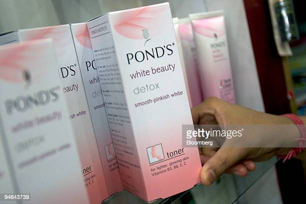 A shop assistant takes a box of Ponds 'White Beauty' Toner produced by Hindustan Lever Ltd from a shelf in New Delhi India on Monday April 16 2007