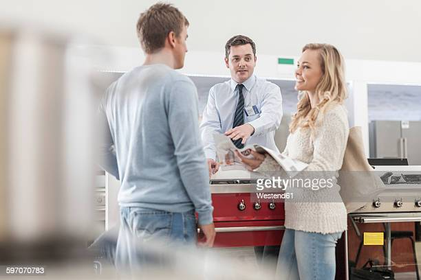 Shop assistant talking to young couple shopping kitchen equipment