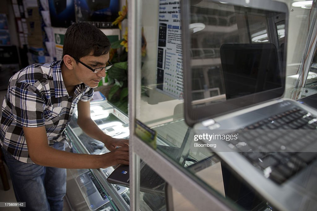 A shop assistant works on a laptop computer in the Afghan Zamin Computer store inside a shopping center for electronic goods in Kabul, Afghanistan, Wednesday, Aug. 7, 2013. A smooth U.S. exit from Afghanistan will depend on Pakistans cooperation with the logistical pullout, as well as its backing for peace talks in neighboring Afghanistan and an end to any support for extremist proxies operating there. Photographer: Victor J. Blue/Bloomberg via Getty Images