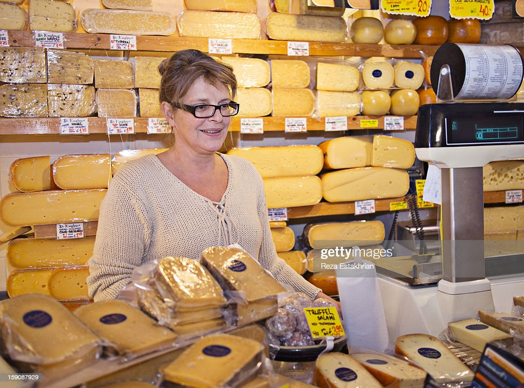Shop assitant smiles at customer : Stock Photo