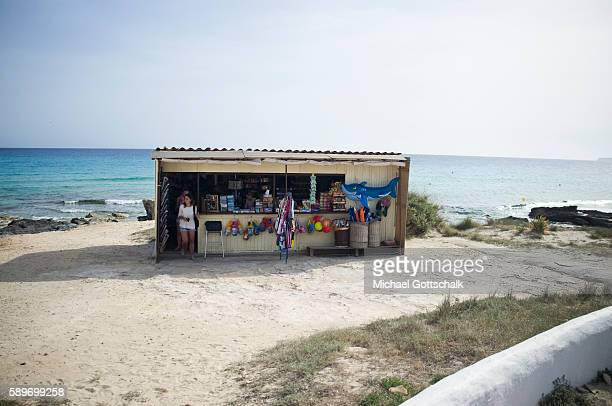 A shop at a beach which sells umbrellas food and a plastic shark on May 12 2016 in Formentera Spain